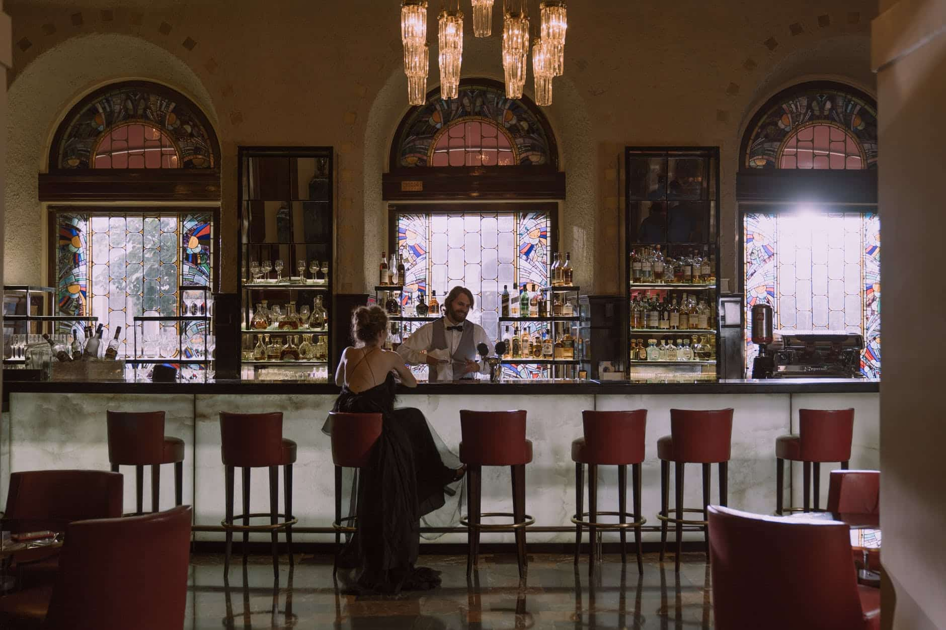 woman in black dress sitting alone at a bar counter